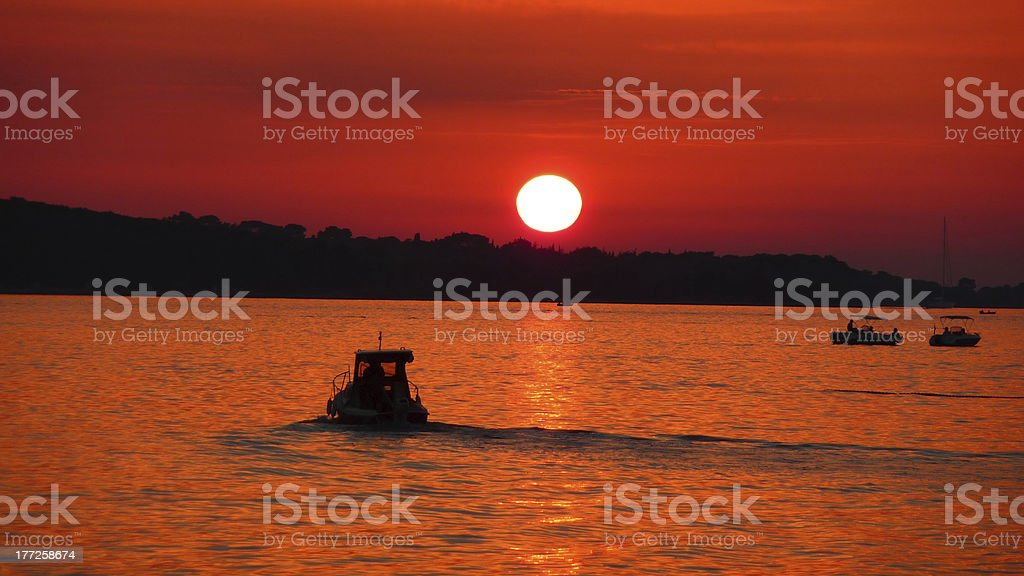 Fishermen on sea at red sunset stock photo