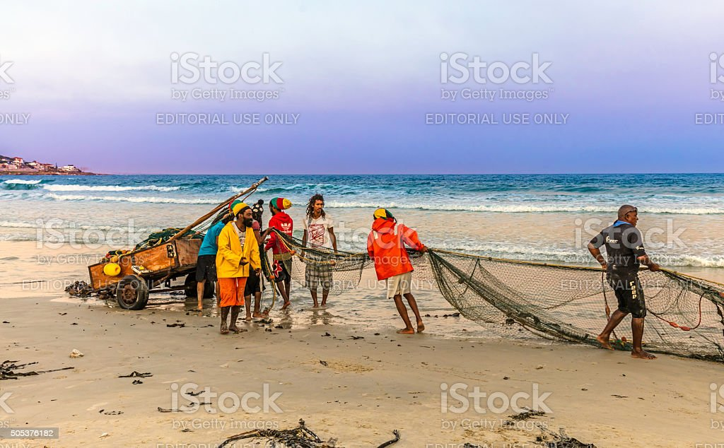 Fishermen pulling in the nets at the beach stock photo