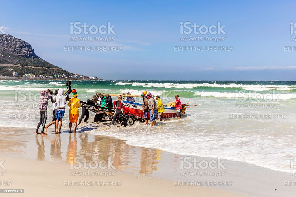Fishermen pulling the boat out from the sea stock photo