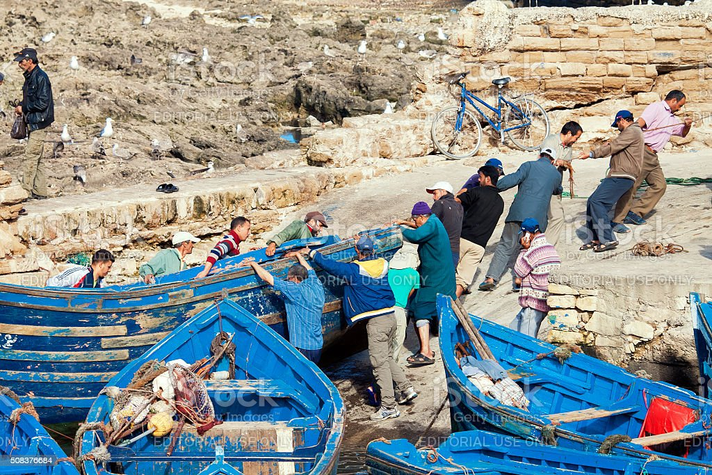 Fishermen pushing a boat repair in fishing port of Essaouira stock photo