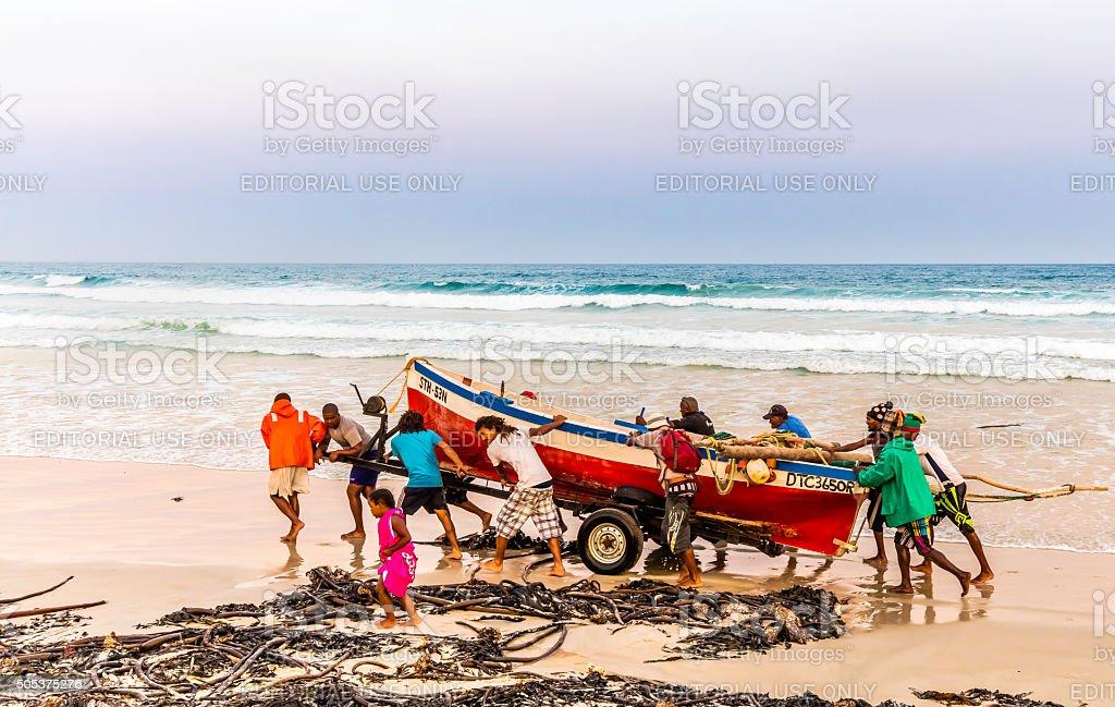 Fishermen pushing their boat along the beach stock photo