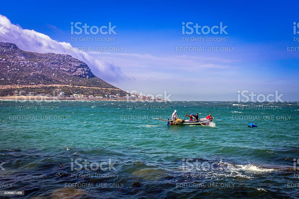 Fishermen rowing a boat out to sea in False Bay stock photo