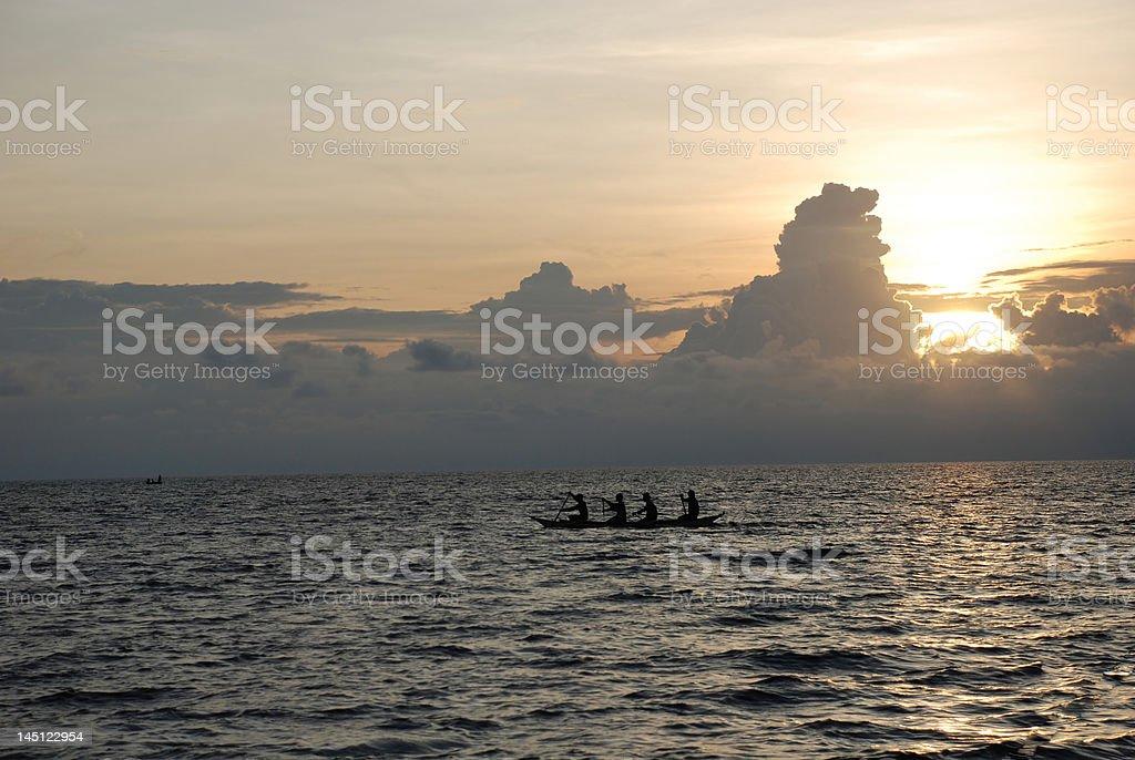 Fishermen rowing at sunset royalty-free stock photo