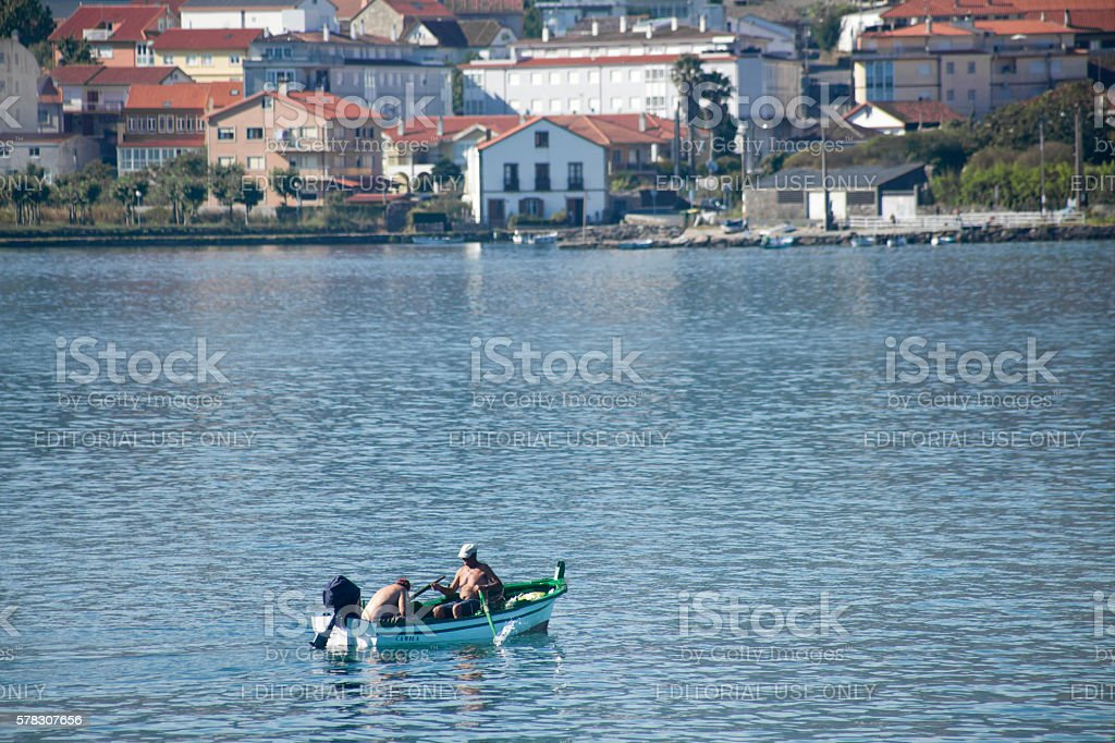 Fishermen rowing, fishing boat, village. stock photo