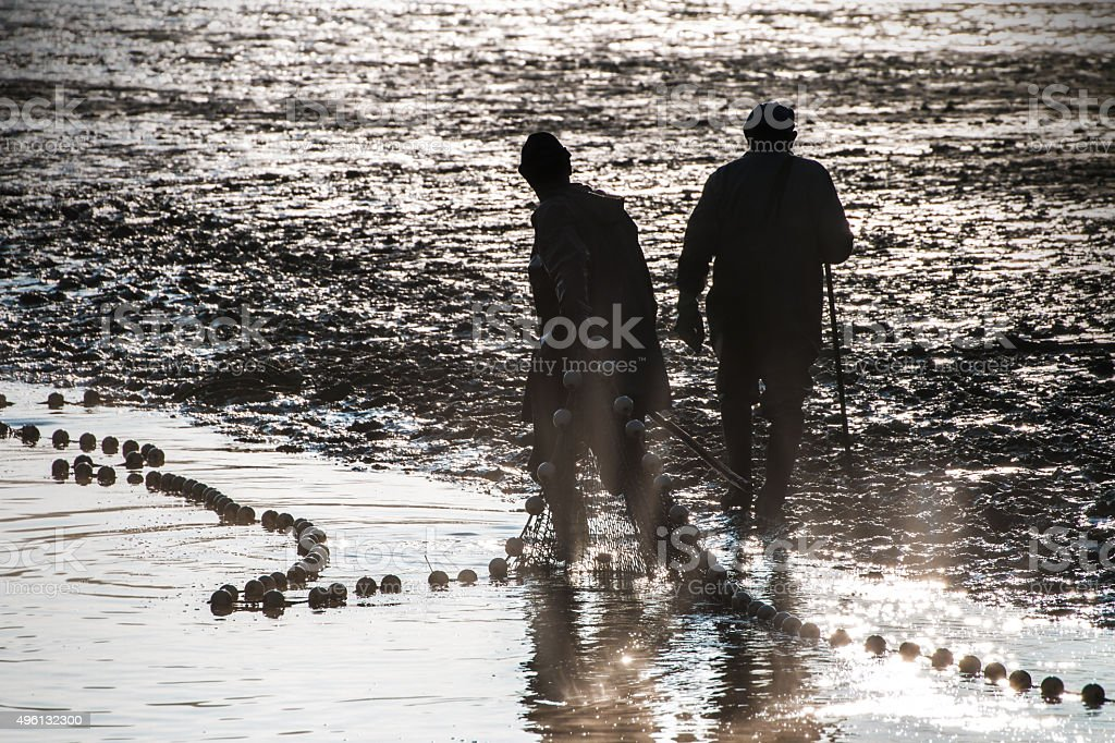 Fishermen silhouette fishing with net in french pond water stock photo