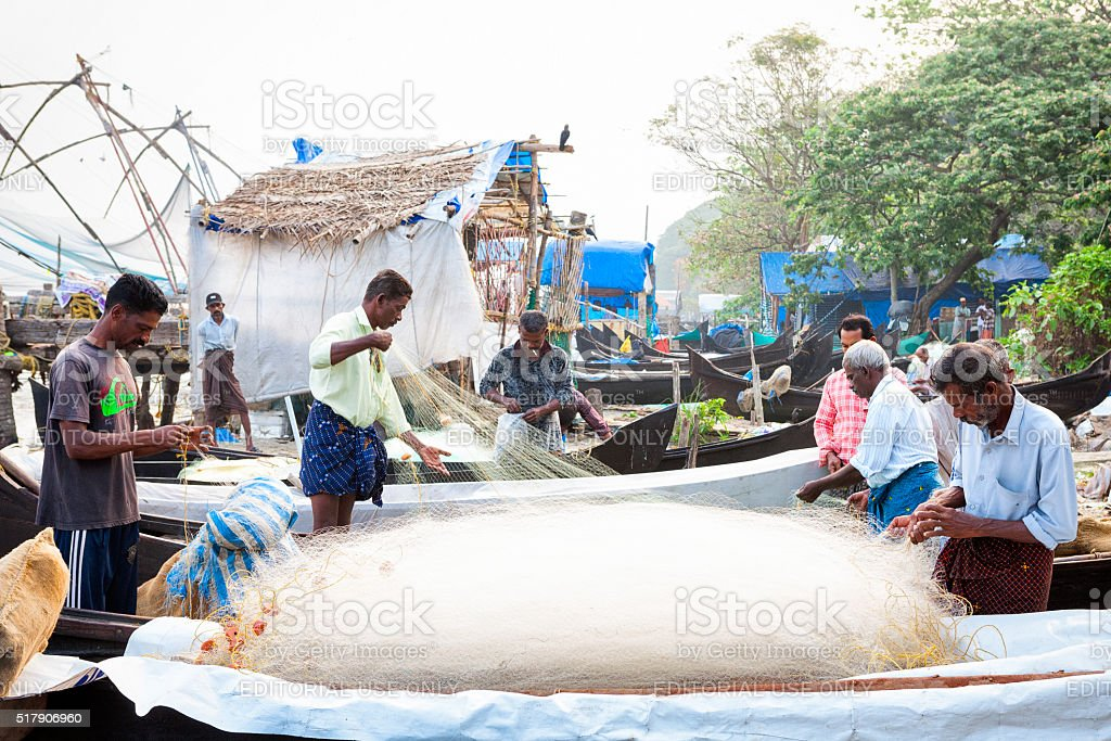Fishermen untangling nets in Kochi, India stock photo