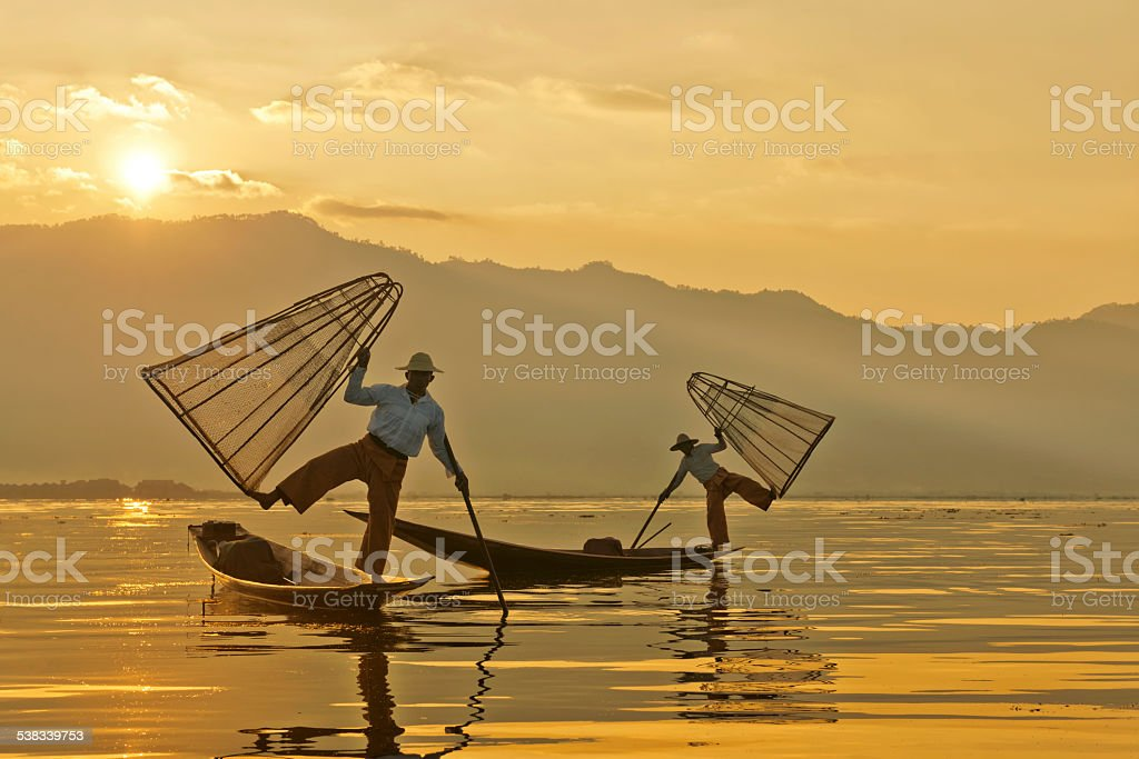 Fishermen With Traditional Fish Traps At Sunrise Over Inle Lake stock photo