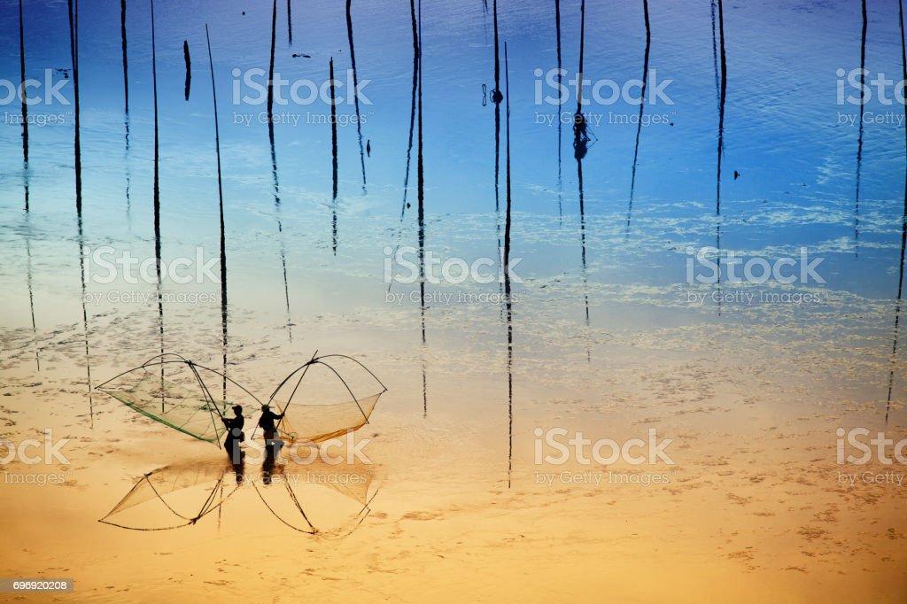 Fishermen working on mud flat in Xiapu, Fujian Province, China. stock photo