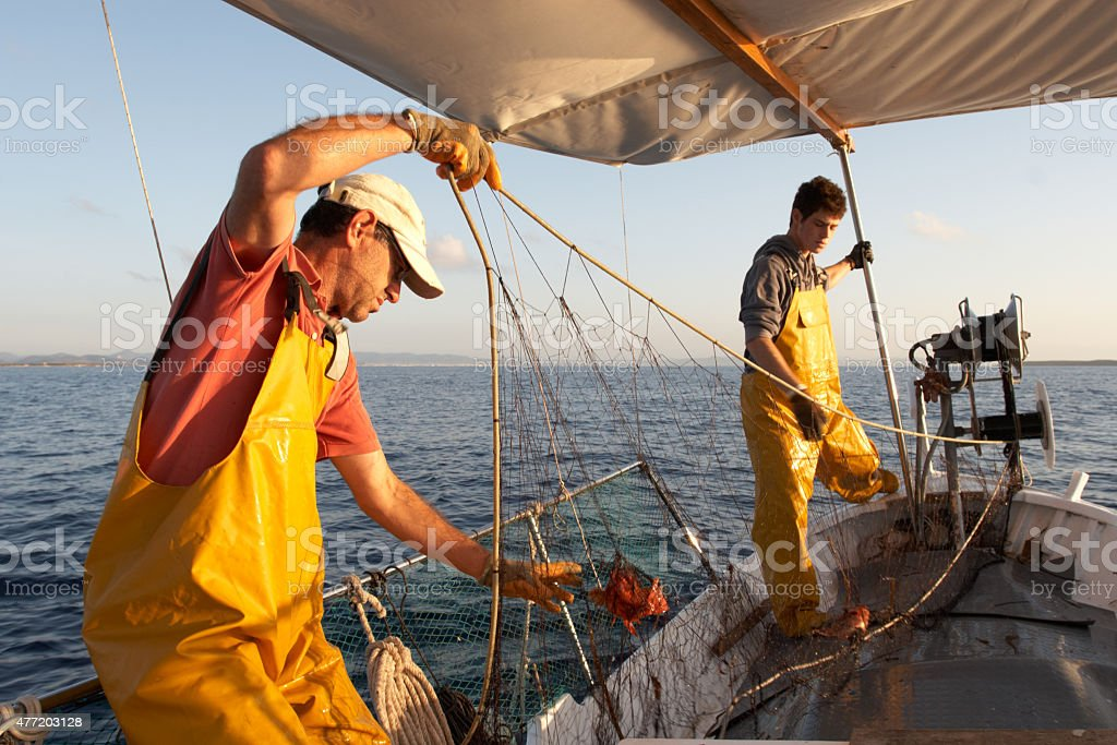 Fishermen working on the boat. stock photo