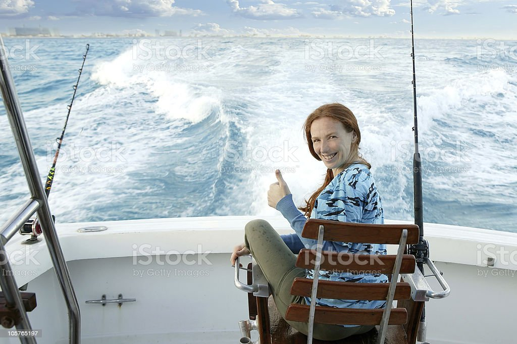 fisherwoman big game on boat chair ok sign royalty-free stock photo