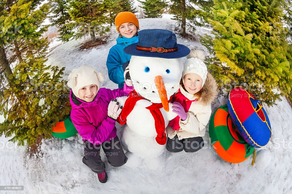 Fisheye view from top of children and snowman stock photo