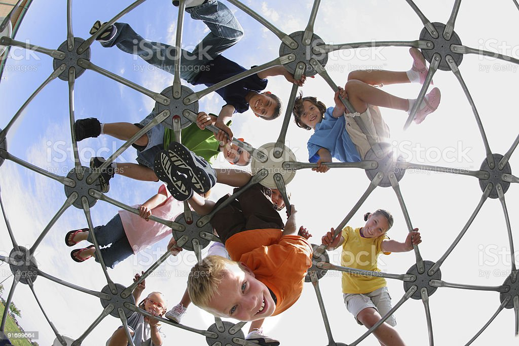 Fish-eye view of children on play equipment stock photo