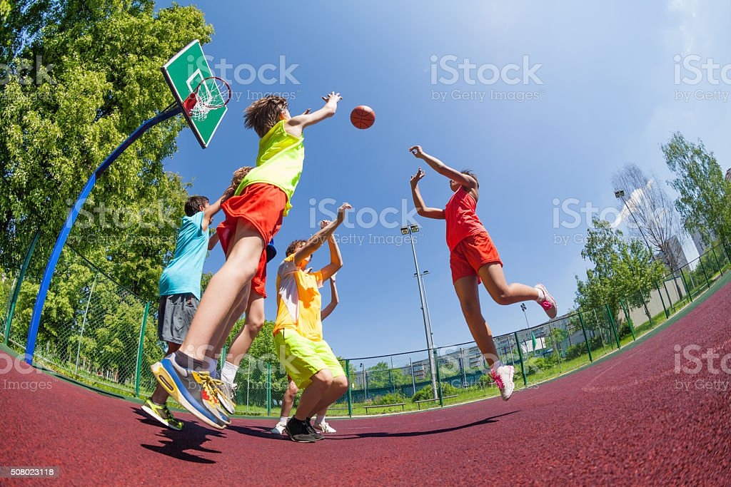 Fisheye view of teenagers playing basketball game stock photo