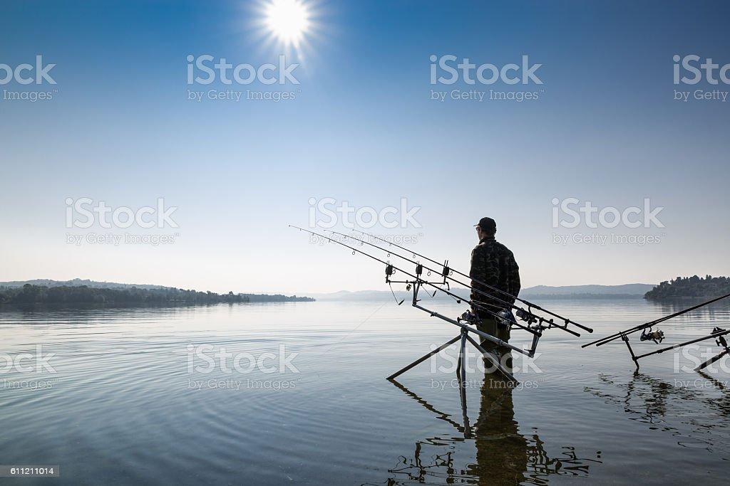 Fishing adventures. Fisherman near the carpfishing equipment stock photo
