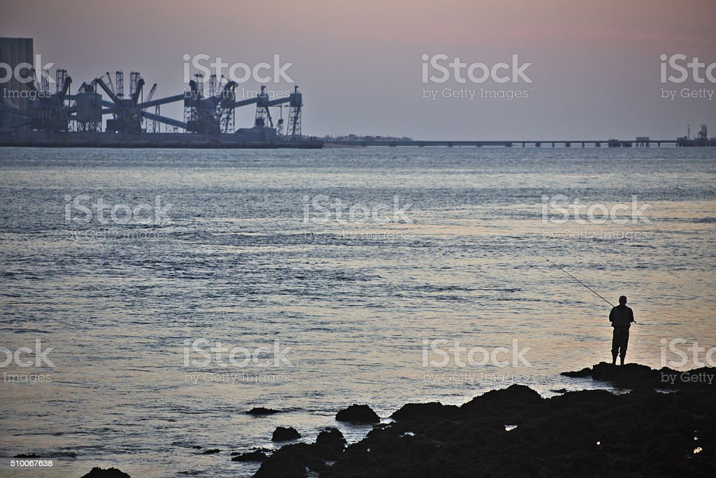 Fishing alone at the mouth of the Tagus river in Lisbon stock photo