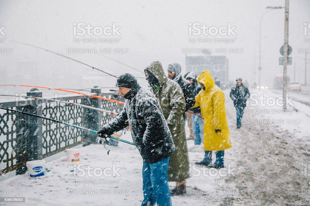 Fishing at Galata Bridge at winter time, Istanbul stock photo
