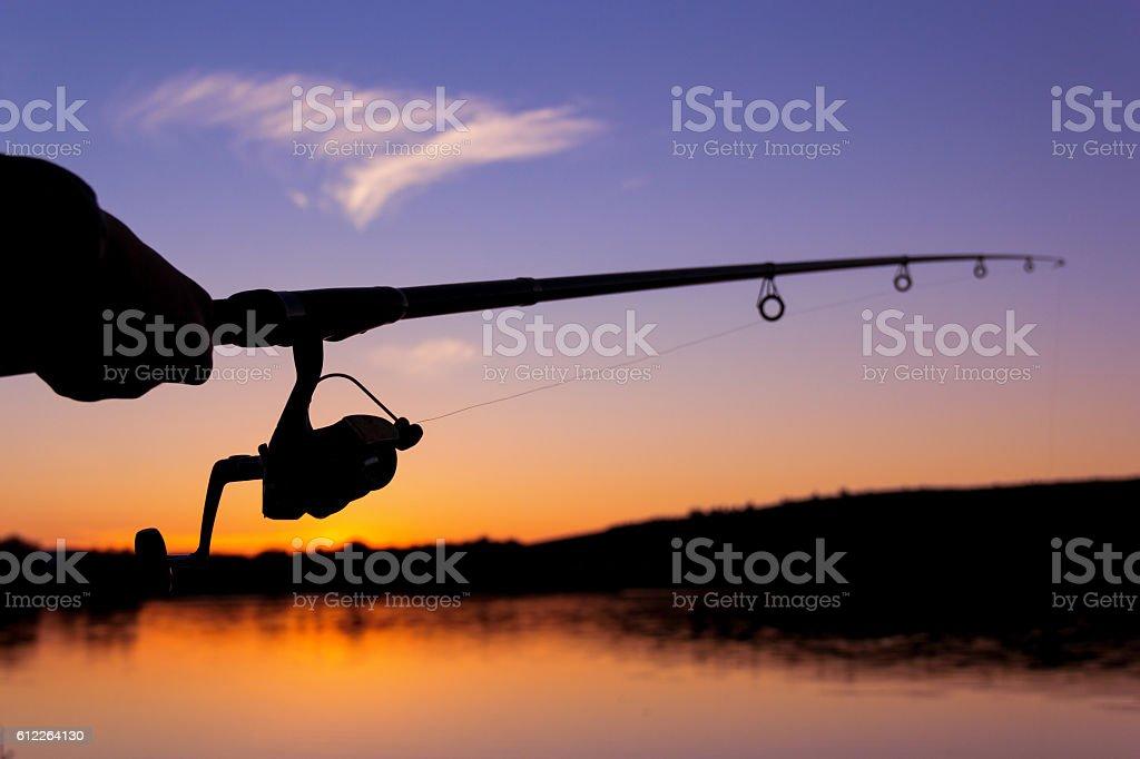 fishing at sunset near the sea stock photo