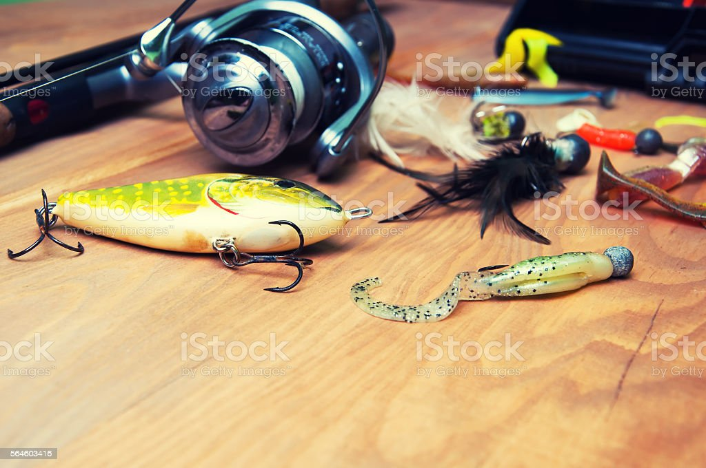 Fishing baits and rod isolated on wooden background stock photo