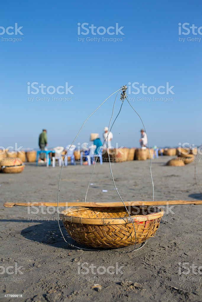 Fishing basket with two woman, wearing conical hat in background royalty-free stock photo