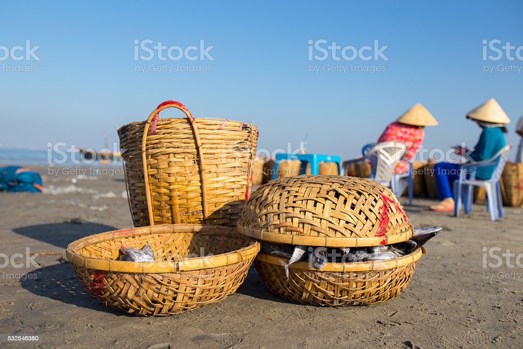 Fishing basket with two woman, wearing conical hat in background stock photo