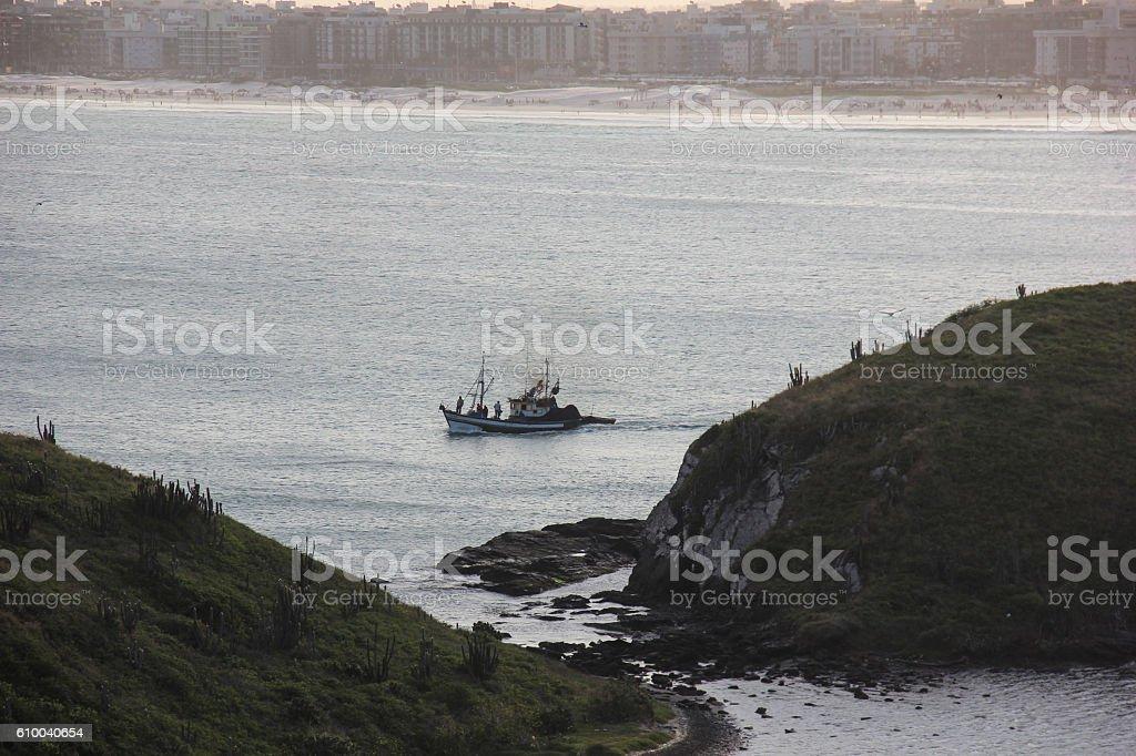 Fishing boat among rocks in the sea stock photo