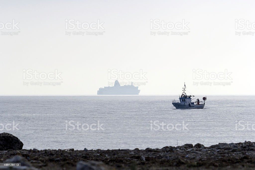 fishing boat and cruise ship stock photo