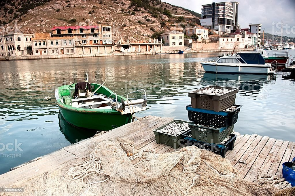 Fishing boat and freshly caught fish in fish crates. stock photo