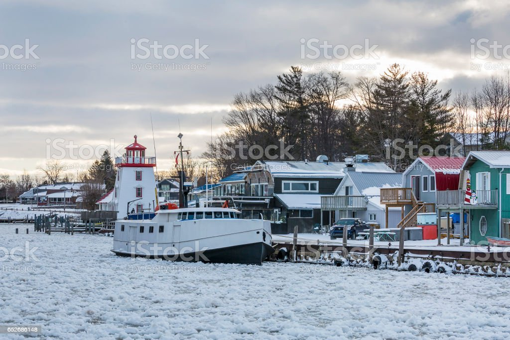 Fishing Boat and Lighthouse in a Lake Huron Harbor in Winter stock photo