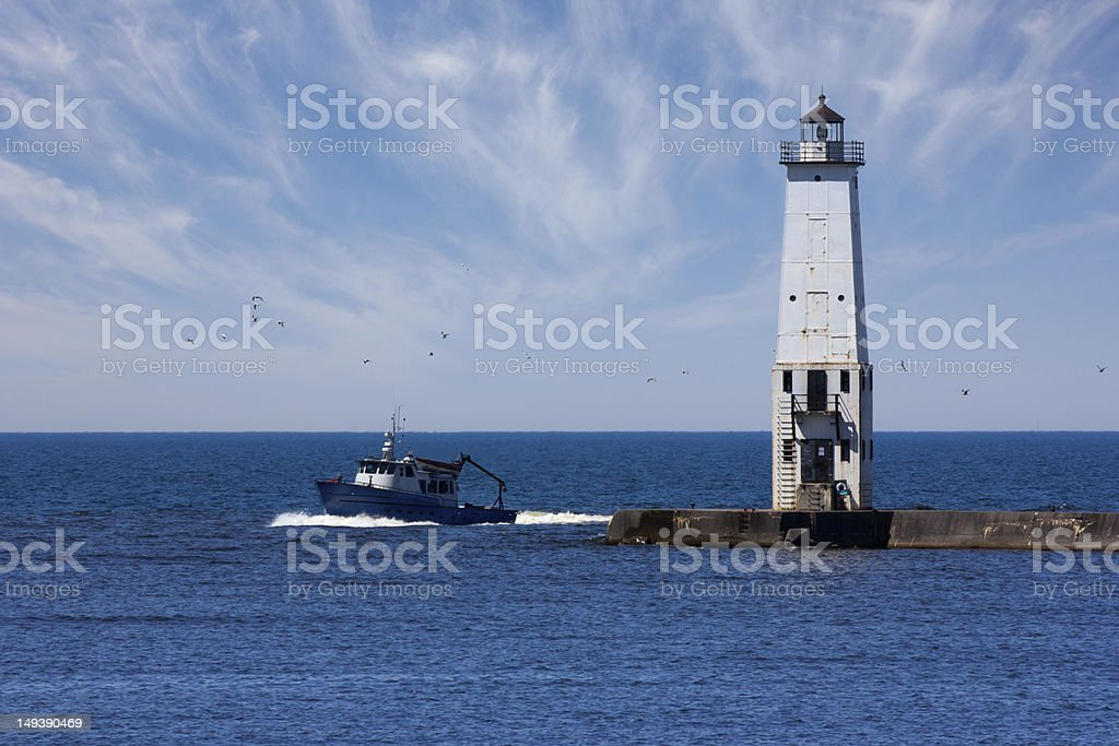 Fishing Boat and Lighthouse royalty-free stock photo