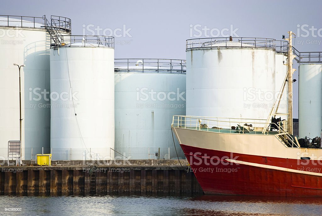 Fishing boat and Oil storage tanks stock photo