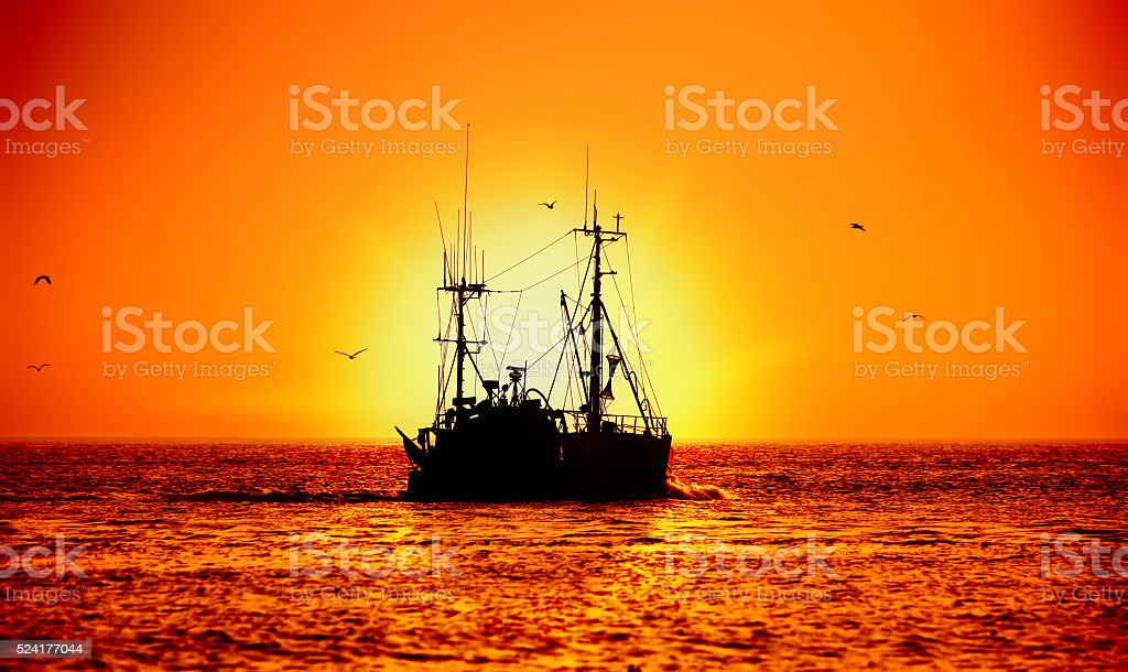 fishing boat and sunset stock photo