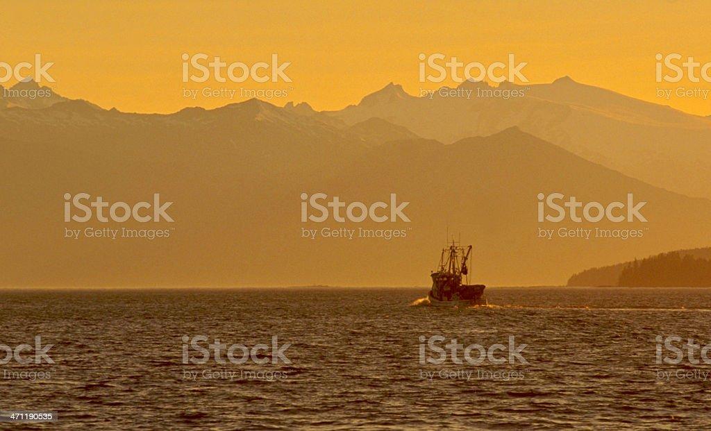 Fishing boat at sunset, Southeast Alaska stock photo