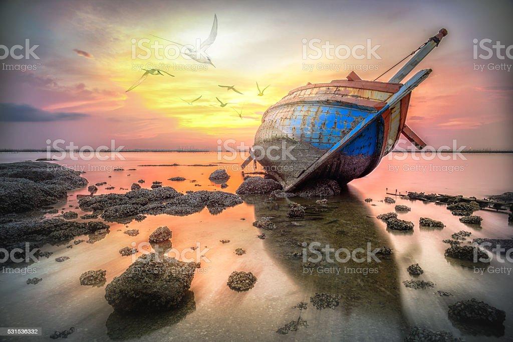 Fishing boat capsize with flying birds, sea sunset stock photo