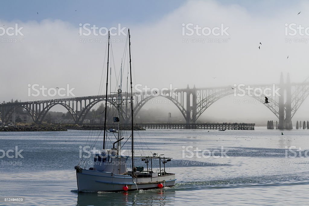 Fishing boat coming out from the mist stock photo
