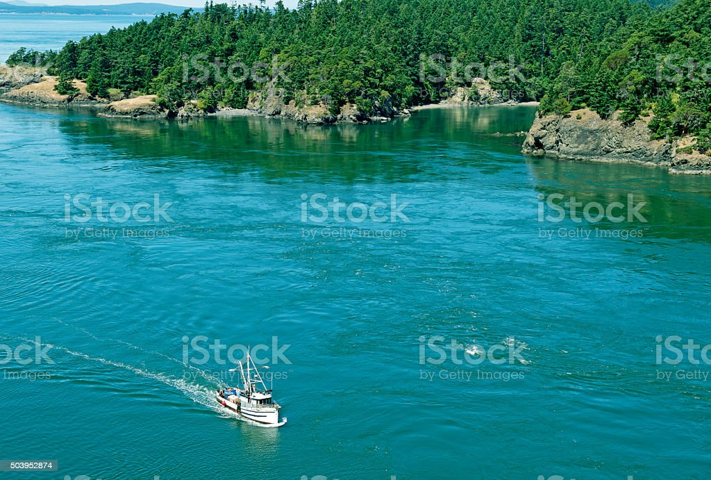 Fishing boat entering Deception Pass on Whidbey Island WA stock photo