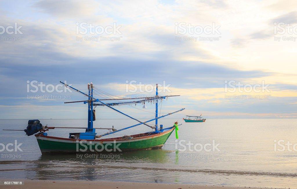 fishing boat floating  in a sand sea with sunrise Стоковые фото Стоковая фотография