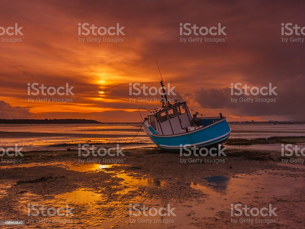 Fishing Boat grounded at low tide in Poole Harbour stock photo