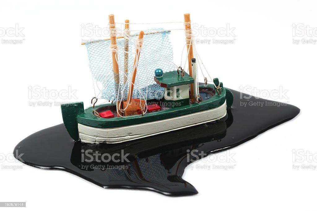 Fishing boat in oil slick stock photo