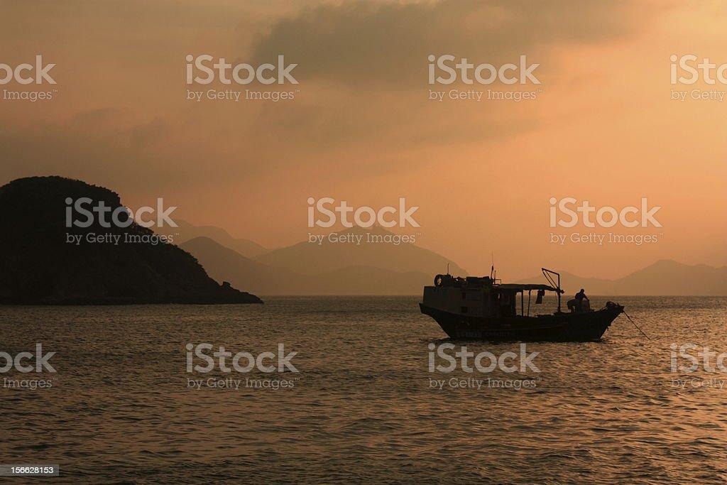 Fishing boat in sunset, Hong Kong. royalty-free stock photo