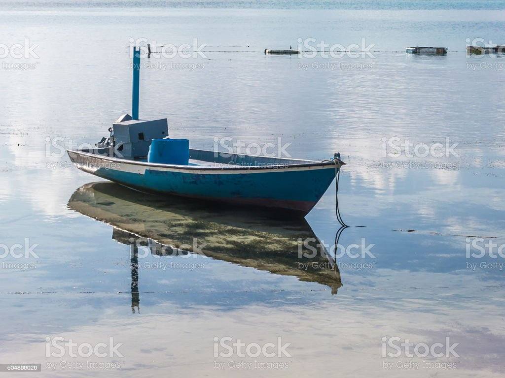 Fishing boat in the water with reflection stock photo