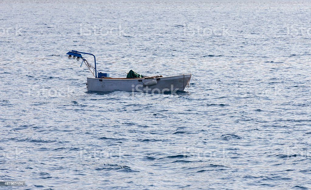fishing boat in the waves stock photo