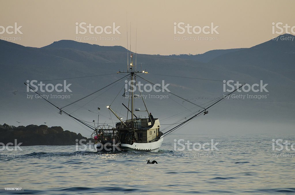 fishing boat leaving harbor, Morro Bay, California stock photo