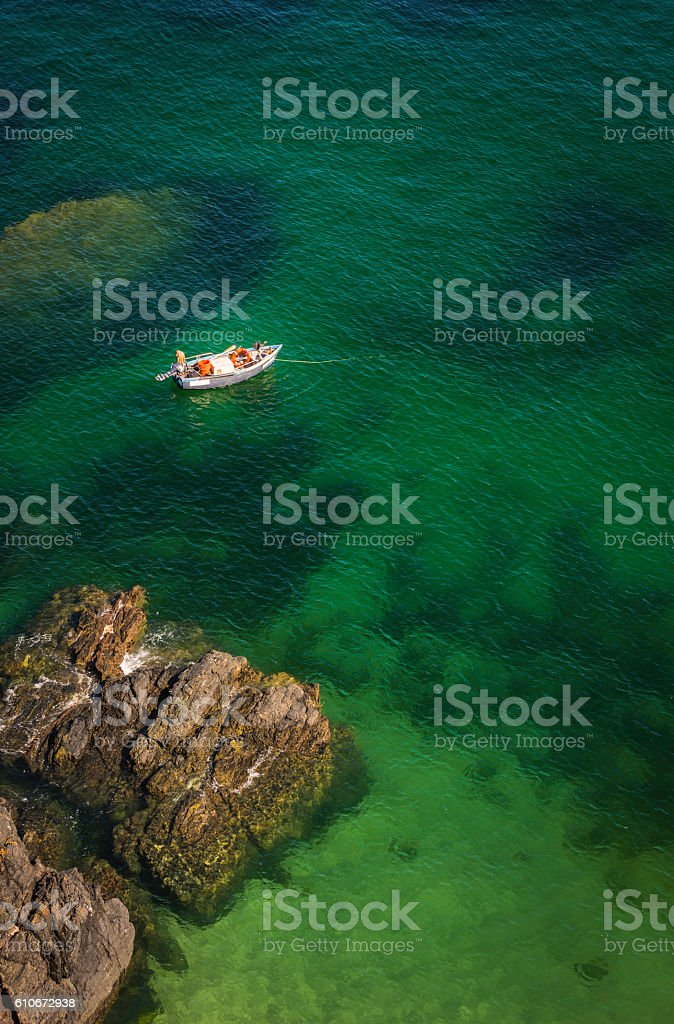 Fishing boat moored on clear ocean waters idyllic rocky bay stock photo