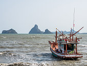Fishing boat moored on the coast sea with mountains background.