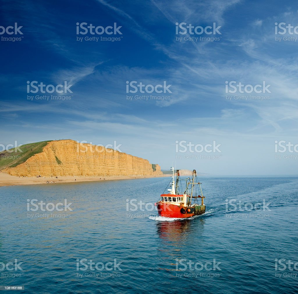 Fishing Boat Moving Through Ocean Near Coastline stock photo