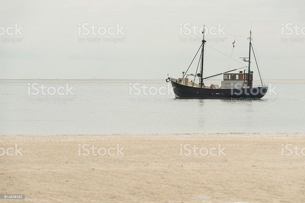 Fishing boat nearby the beach . stock photo