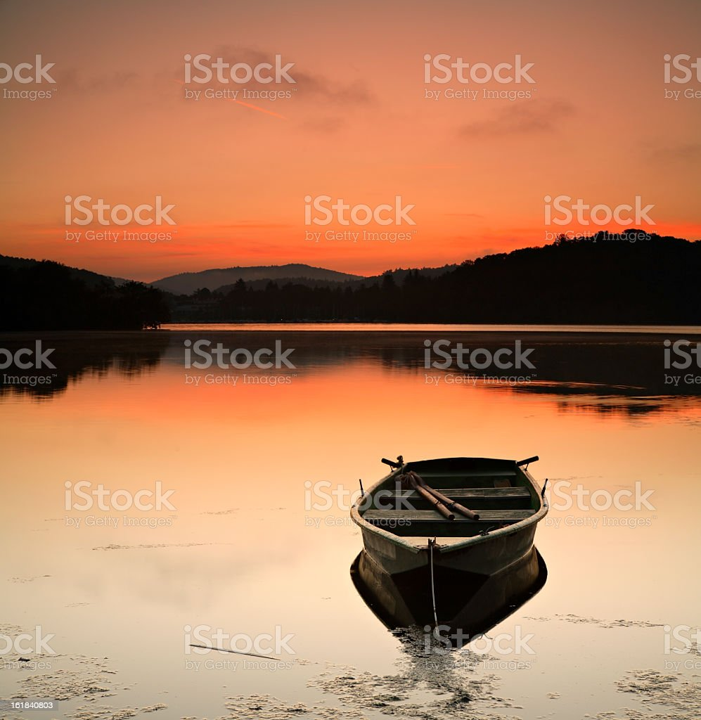 Fishing Boat on Lake at Sunset stock photo