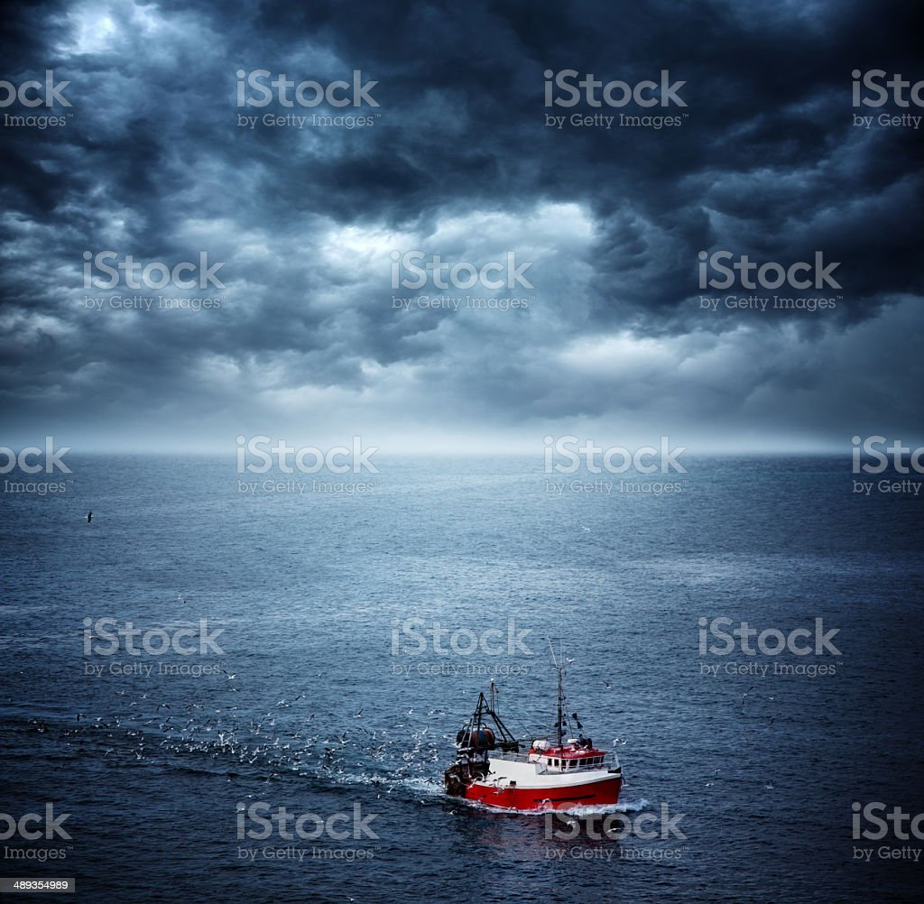 fishing boat returning home before sea storm stock photo