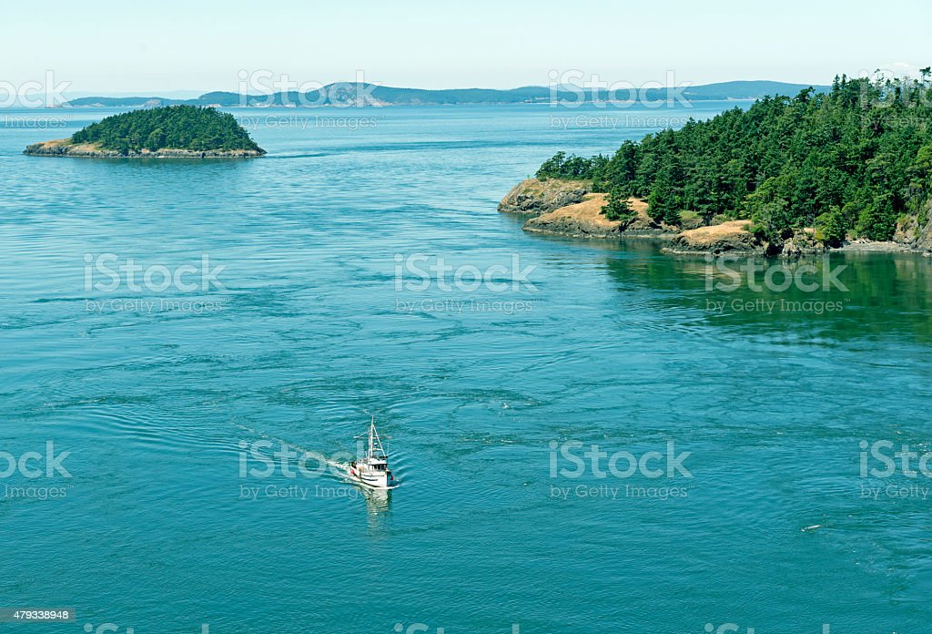 Fishing boat returning through outgoing tide in Washington state stock photo