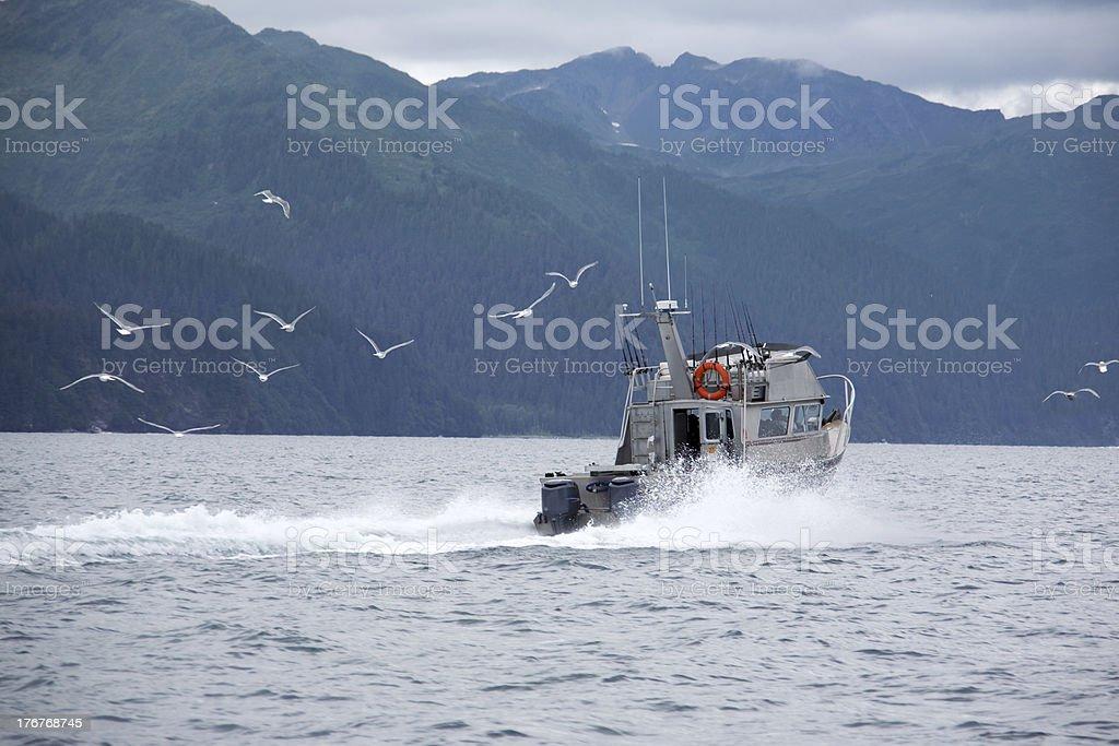 Fishing boat returning to port in Alaska stock photo